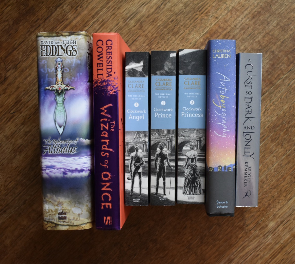 Photo of book spines. Books are The Redemption of Althalus, The Wizards of Once, Clockwork Angel, Clockwork Prince, Clockwork Princess, Autoboyography, and A Curse So Dark and Lonely.